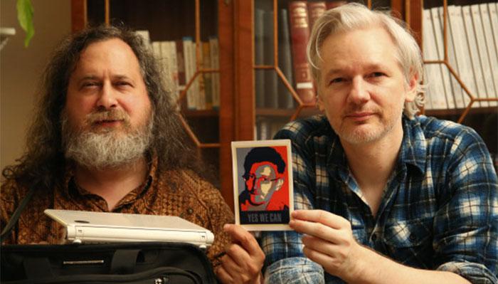 Foto histórica de Richard Stallman (padre del Software Libre) y Julian Assange sosteniendo una foto de Edward Snowden.